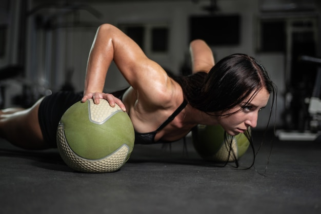 Fitness girl does push-ups on the ball