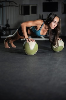 Fitness girl does push-ups on the balls