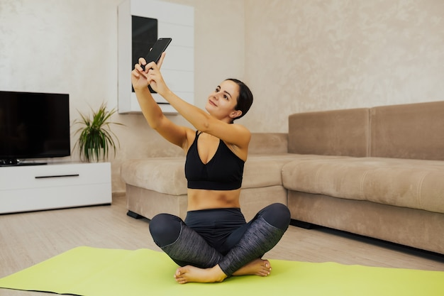 Fitness girl does selfie after training at home. female athlete relaxing after workout.