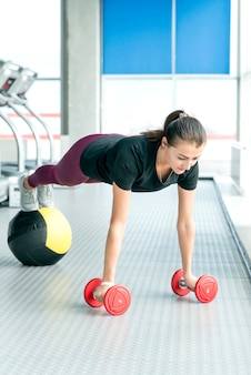 Fitness girl doing dumbbells and medicine ball plank. woman doing floor workout at gym