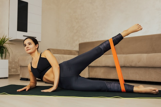 Fitness girl doing leg workout exercises with rubber strap elastic.
