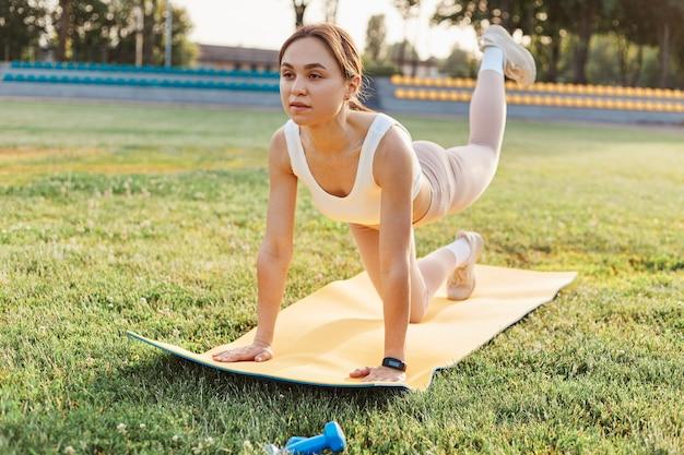 屋外スタジアムでヨガマットの脚のトレーニングをしているフィットネスの女の子、白いトップとベージュのレギンスを一人でトレーニングしているフィットの女性、ヘルスケア、健康的なライフスタイル。