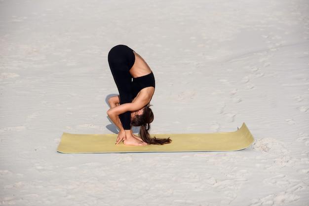 ビーチでストレッチを行うフィットネス女の子。ヨガマットでウォームアップを行う女性アスリート。スポーツヨガと健康的なライフスタイルのコンセプト。
