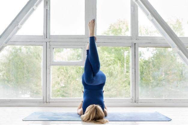 Fitness girl doing yoga asana in class