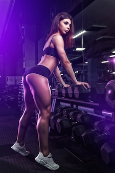 Fitness girl exercising and posing with barbell in gym.