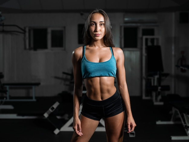 Fitness girl exercising with barbell, woman posing in gym