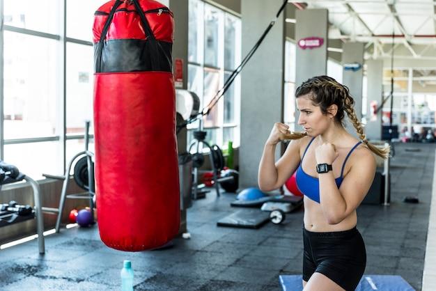 Fitness girl hitting punching bag