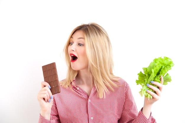 Девушка фитнеса в клетчатой рубашке с красной помадой держит зеленый свежий салат-латук и кусает шоколад, диету и концепцию здоровья на фоне белой стены