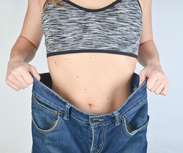 大きくて広いジーンズに挑戦するスポーツトップスのフィットネス女の子。減量のコンセプト。
