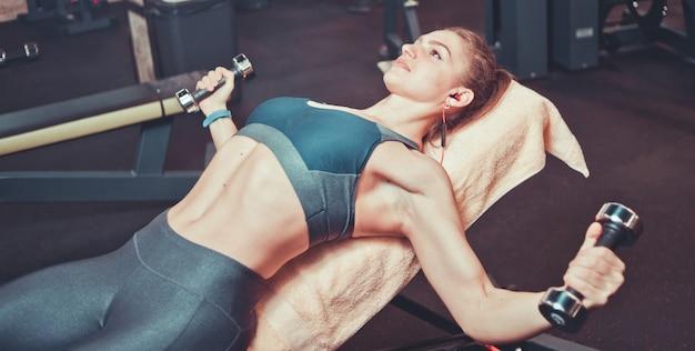 ジムで傾斜したベンチにダンベルでスポーツウェアトレーニングでフィットネス女の子。胸筋トレーニング