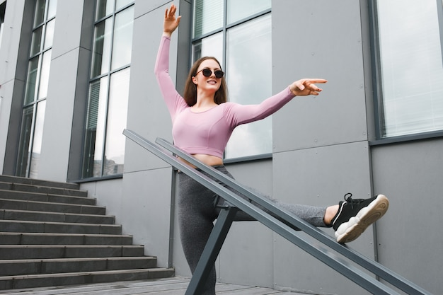 Fitness girl is stretched on the stairs