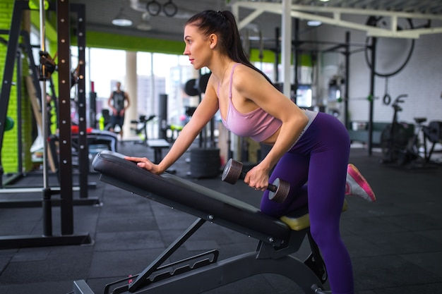 Fitness girl lifting dumbbell in the morning .
