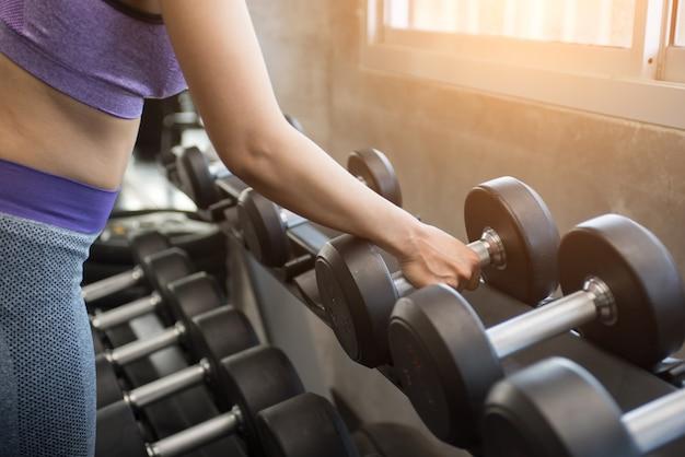 Fitness girl lifting dumbbell.