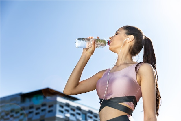 Fitness girl listening to a music drinks water