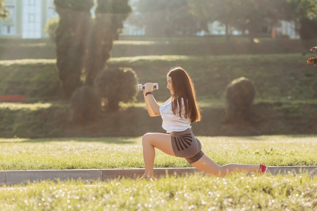 Fitness girl making exercises with dumbbells on sunset at grass outside