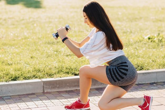 Fitness girl making exercises with dumbbells on sunset at grass outside