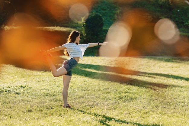 Fitness girl making stretching exercises outside on sunshine an grass