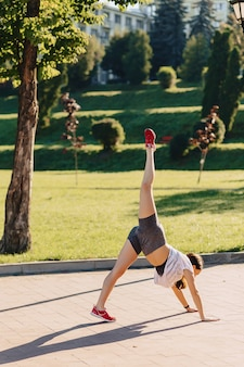Fitness girl making stretching at park at morning sunshine