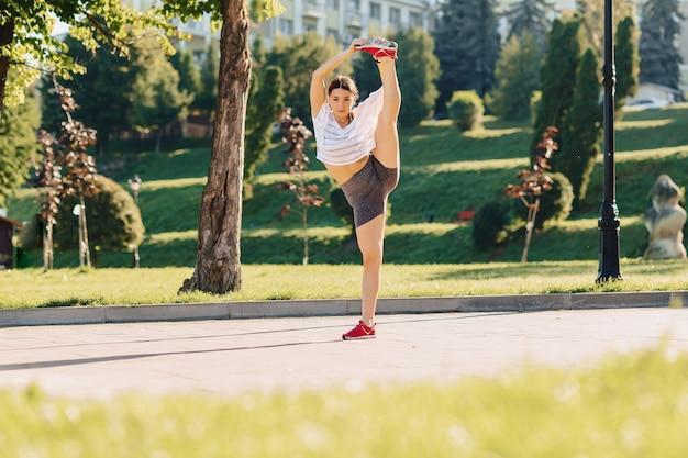 Fitness girl making stretching at park at morning sunshine