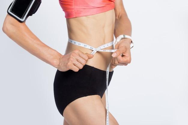 Fitness girl measuring her waist