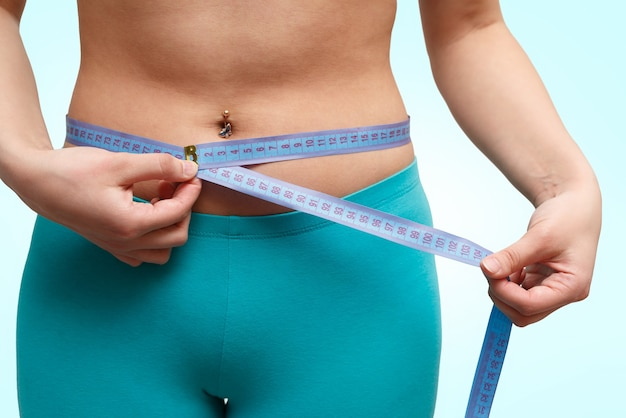 Fitness girl measuring waist by a centimeter on a blue background