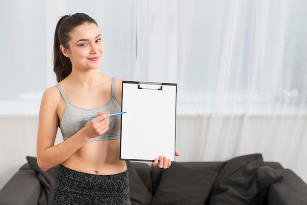Fitness girl pointing at folder