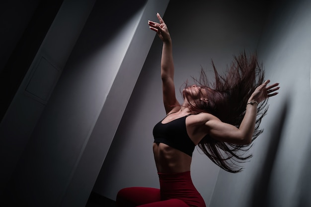 Fitness girl posing on a gym ball near the wall, showing a body and flying hair