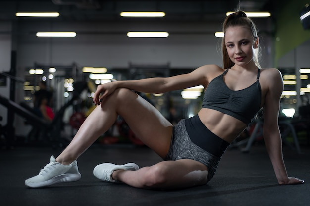 Fitness girl posing in the gym sitting on the floor showing off her body