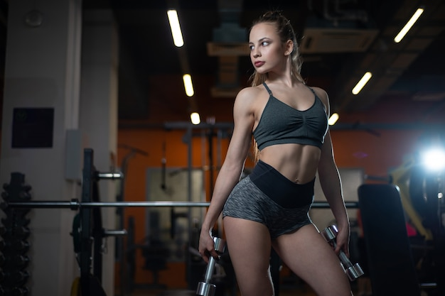 Fitness girl posing in the gym with dumbbells in her hands, showing off her body