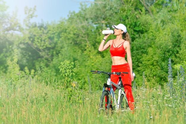 Фитнес девушка отдыхает возле велосипеда на открытом воздухе и пьет воду из бутылки
