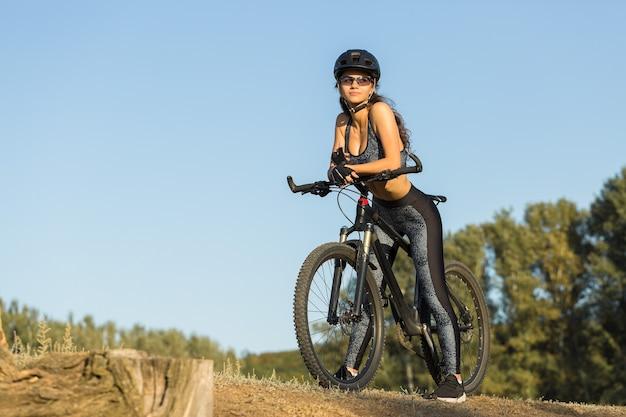 피트니스 소녀는 들판에서 운동복을 입고 현대적인 탄소 섬유 산악 자전거를 탄다