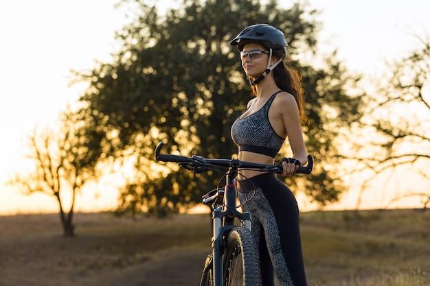 피트니스 소녀는 운동복을 입고 현대적인 탄소 섬유 산악 자전거를 탄다.