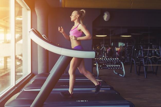 Фитнес девушка работает на беговой дорожке