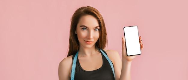 피트니스 소녀 미소하고 모형과 함께 전화를 들고 분홍색 벽에 검은 색 운동복에 보류 측정 테이프를 포즈