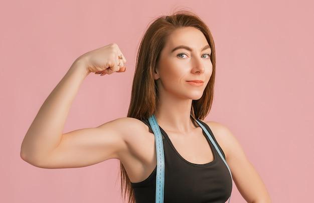 ピンクの壁に黒いスポーツウェアのメジャーテープを笑顔でポーズをとっているフィットネスの女の子