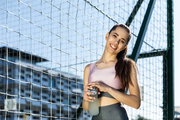 Fitness girl smiling holds bottle of water