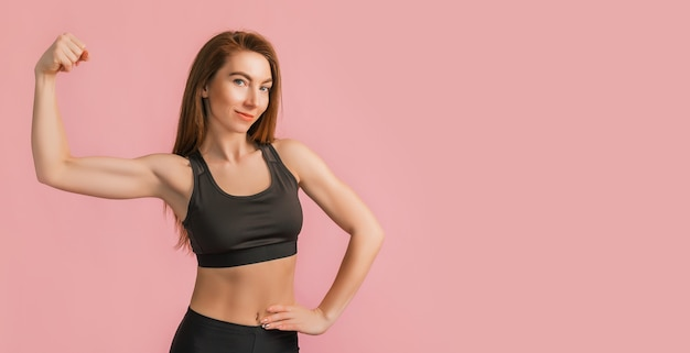 ピンクの背景に黒のスポーツウェアで笑っているフィットネスの女の子。美しいアスリートボディと日焼けした肌を持つスリムな女性