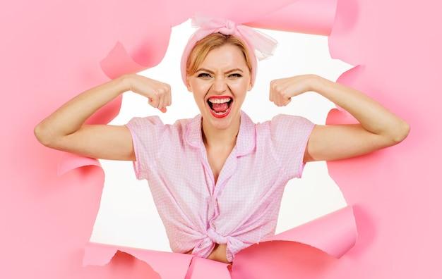 Девушка фитнеса. улыбающаяся женщина, показывая ее бицепс. сильная девушка сгибает мышцы.