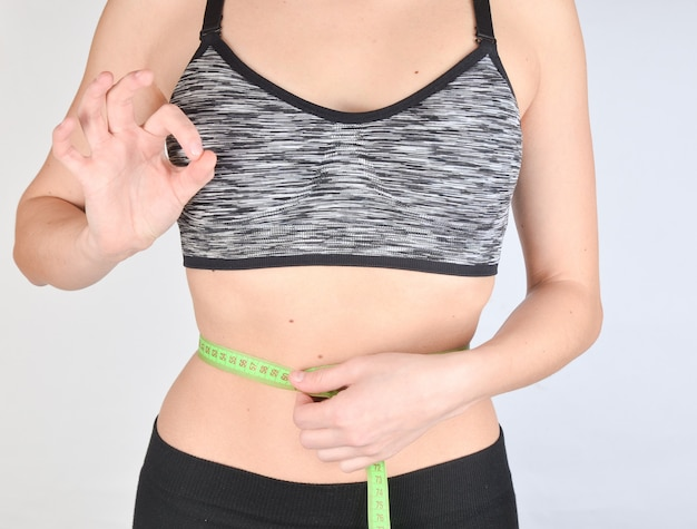 Fitness girl in sports tops measuring ruler waist. the concept of losing weight.