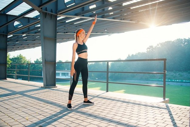 Fitness girl at sportswear makes exercises in the background of sport stadium. warm up before training. young sports girl makes stretching.