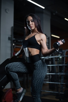 Fitness girl trains biceps with dumbbells in the gym.