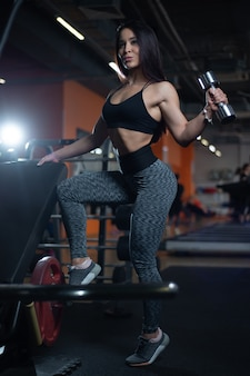 Fitness girl trains biceps with dumbbells in the gym,