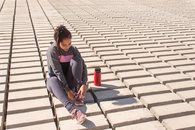 海岸で休んで、靴ひもを結ぶフィットネスの女の子。