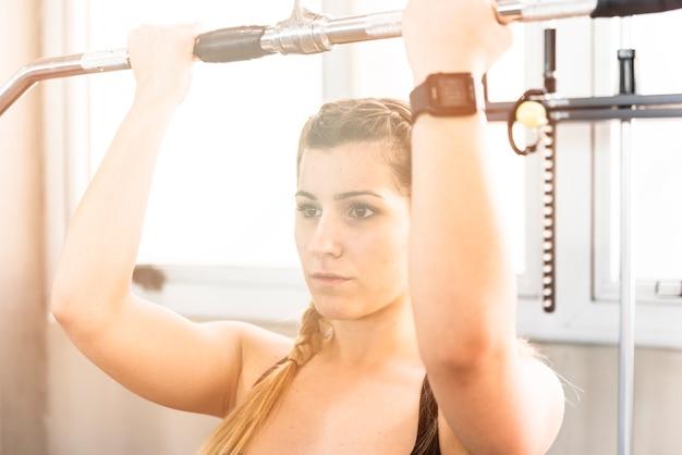 Fitness girl using weight machine