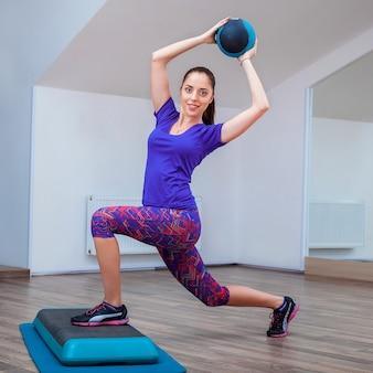 Фитнес девушка, одетая в кроссовки, ставит на ступеньку с мячом