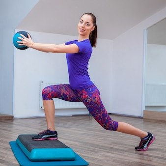 Fitness girl, wearing sneakers posing on step board with ball