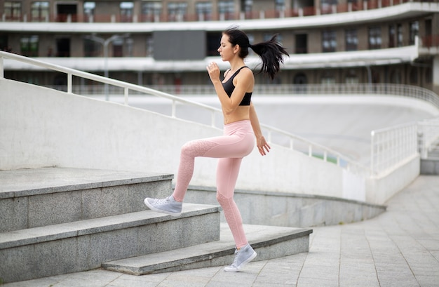 Fitness girl wears sports clothes jumping on stairs during her morning workout. empty space