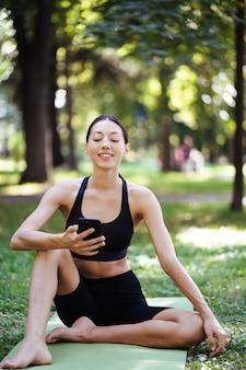 自然の背景にスマートフォンを持つフィットネスの女の子は、スポーツトレーニングを楽しんでいます。屋外で携帯電話を使用している女性。