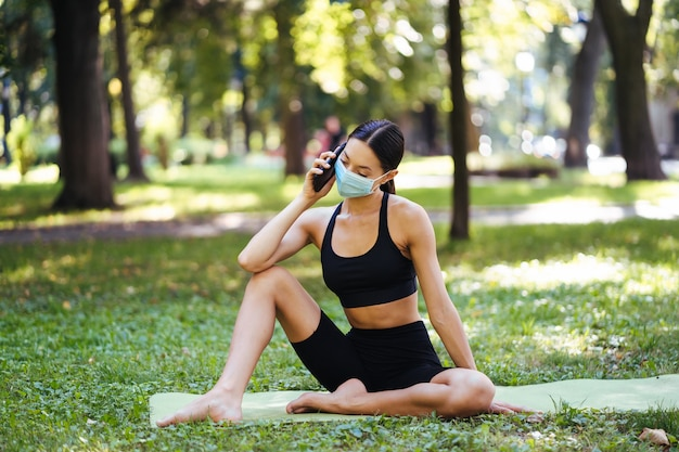 자연 배경에 스마트 폰으로 피트니스 소녀 스포츠 훈련을 즐깁니다. 야외에서 핸드폰을 사용하는 여자.
