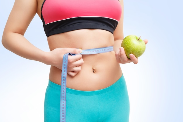 Fitness girl with centimeter and apple in hand